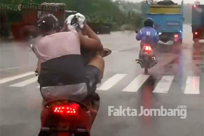 aksi keramas di atas motor di jalan raya mojoagung jombang